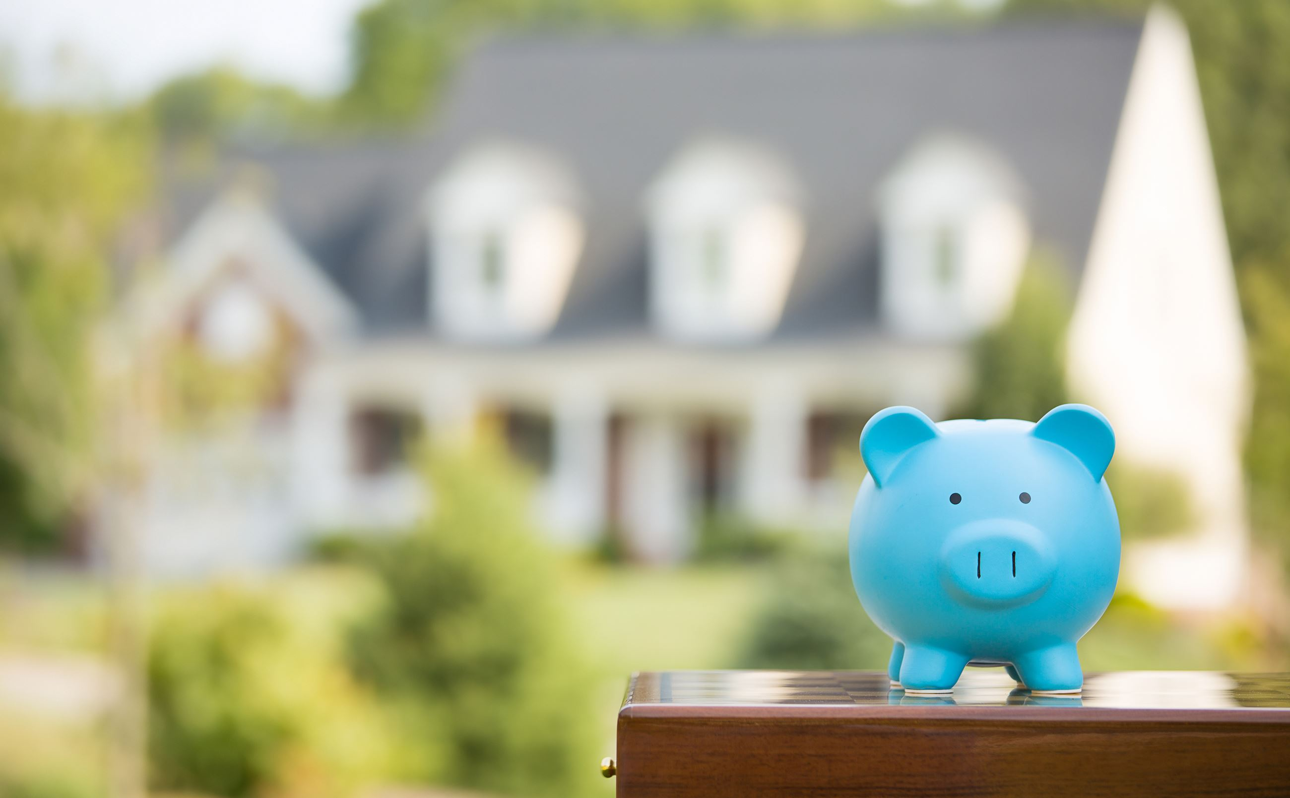 Image of piggy bank with house in background